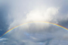Rainbow and clouds. A dramatic sky with a clear and bright rainbow Stock Image