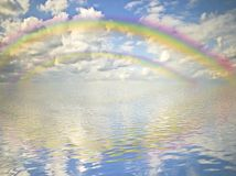 Rainbow, cloudy sky and ocean Royalty Free Stock Image