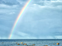 Rainbow in cloudy sky after the rain Stock Photo