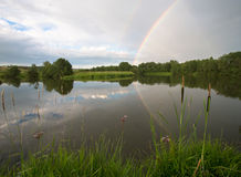 Rainbow on cloudy sky with river Royalty Free Stock Photo