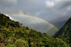 Rainbow on cloudy sky , trees foreground, Sikkim. Rainbow on cloudy sky , with green trees in foreground, Sikkim Royalty Free Stock Photography
