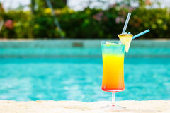 Rainbow cocktail at the edge of a resort pool.  Concept of luxur Royalty Free Stock Photography