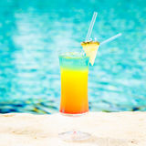 Rainbow cocktail at the edge of a resort pool.  Concept of luxur Royalty Free Stock Images