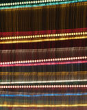 Rainbow color night. Motion blur effect from party lights in front of a black night sky, with an added layer of detailed, shining lamps on it royalty free stock photos