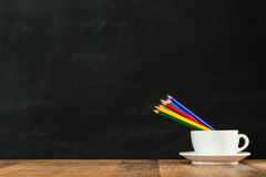Rainbow color pencils in the white coffee cup. Rainbow color pencils in white coffee cup performance back to school concept with wood texture retro table on Royalty Free Stock Photography