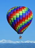 Rainbow Colored Balloon Over the Rockies. A rainbow colored hot air balloon floats above the Rocky Mountains Royalty Free Stock Image