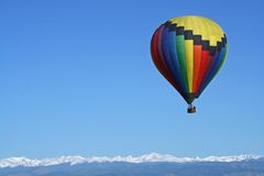 Rainbow Colored Balloon Over the Rockies. A rainbow colored hot air balloon floats above the Rocky Mountains Stock Photo