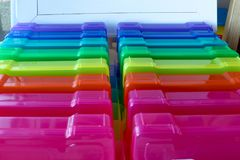 Rainbow colored boxes for organizing. Line of rainbow colored boxes for organizing photos and small items against a white wood background Stock Images