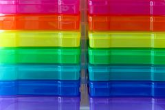 Rainbow colored boxes for organizing. Line of rainbow colored boxes for organizing photos and small items against a white wood background Royalty Free Stock Photo