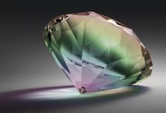 Rainbow colored diamond. Studio photography of a glass diamond in rainbow colors in dark gradient back with clipping path Stock Photo