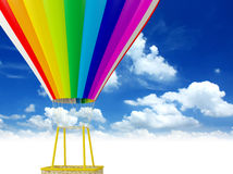 Rainbow Colored Hot Air Balloon. A rainbow colored hot air balloon floats in a blue sky Royalty Free Stock Photo