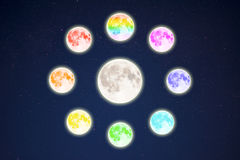 Rainbow colored moons around the full moon on starry sky Stock Images