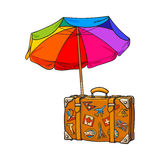 Rainbow colored, open beach umbrella and travel suitcase with luggage stickers Royalty Free Stock Photography