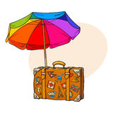 Rainbow colored, open beach umbrella and travel suitcase with luggage stickers Stock Photo