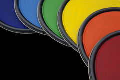 Rainbow colored paint can lids against black background Stock Photos