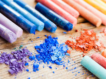 Rainbow colored pastel crayons with crushed chalk close up Royalty Free Stock Photography
