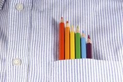 Rainbow of colored pencils in shirt pocket. Set of colored pencils in a shirt pocket, showing red, orange, yellow, green, blue and violet colors Royalty Free Stock Photos