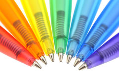 Rainbow of colored pens. Seven automatic colored ballpoint pens with springs in a row Stock Image