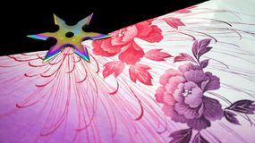 Rainbow shuriken. A rainbow colored shuriken sitting on colorful flowery silk Royalty Free Stock Images