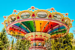 A rainbow colored swing carousel at an amusement park. Royalty Free Stock Photography
