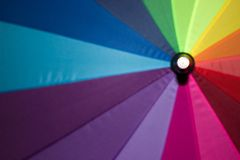Rainbow colored umbrella in smooth focus, opened on the background royalty free stock photography