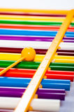 Rainbow colored wooden toy xylophone against white background Royalty Free Stock Photography