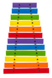 Rainbow colored wooden toy xylophone against white background Stock Photos