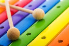 Rainbow colored wooden toy xylophone against white background Stock Images