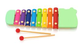 Rainbow colored wooden toy xylophone isolated on white background with shadow reflection. Colorful wooden metallophone toy royalty free stock photography