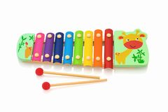 Rainbow colored wooden toy xylophone isolated on white background with shadow reflection.