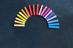 Rainbow of colorful chalks lined up rounded on circle Stock Photo