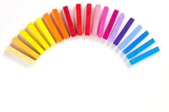 Rainbow of colorful chalks and pastels lined up rounded on circle