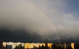 Rainbow. Colorful rainbow on the dark sky above the block of flats after the rain in spring Stock Photo