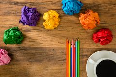 Rainbow colorful paper balls and color pencils. Many rainbow colorful paper balls and color pencils on wooden desk background to showing advertising copyspace Stock Photos