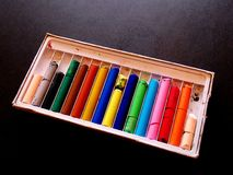 A rainbow of colorful, wear worn oil pastels. In their box on a dark surface Stock Photography