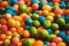 Rainbow colors on background of bright candy small round forms. Abstract sweets with raisins or nuts stuffing Royalty Free Stock Photo