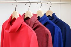 Rainbow colors. Choice of casual clothes on wooden hangers in a store Stock Photography
