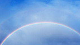 Rainbow colors within clouds Stock Images