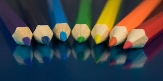 Rainbow colors in pencils. Seven colors of the rainbow pencils on a dark blue glossy background Stock Image