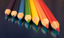 Rainbow colors in pencils. Seven colors of the rainbow pencils on a dark blue glossy background Stock Photography