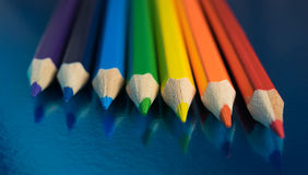 Rainbow colors in pencils. Seven colors of the rainbow pencils on a dark blue glossy background Stock Photos