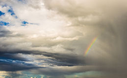 Rainbow in coloured cloudy sky Stock Image
