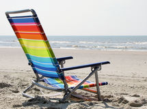 Rainbow colours beach chair on the sand, ocean Stock Images