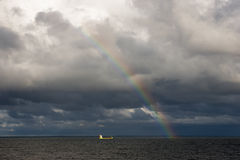 Rainbow and container ship over Sea Royalty Free Stock Photos