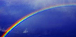 Rainbow contro cielo blu immagini stock libere da diritti
