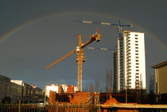 Rainbow and crane. After the heavy rains site appeared over the rainbow construction development foundation construction site after the rain future semicircle Royalty Free Stock Photography