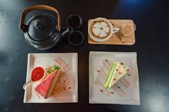 Rainbow crape cake and strawberry sauce on white plate with a cup of hot coffee on dark wooden table. stock photo