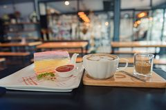 Rainbow crape cake and strawberry sauce on white plate with a cup of hot coffee on dark wooden table. stock photos