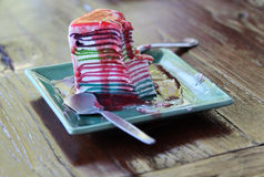 Rainbow crape cake. On wooden table some parts is being eaten Royalty Free Stock Photography