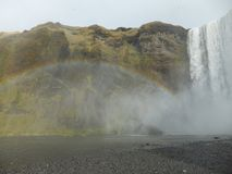 Rainbow created by mist coming from Skógafoss waterfall, Iceland royalty free stock photos